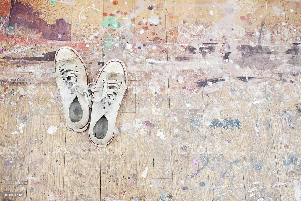 Sneakers on paint-spattered wood floor stock photo