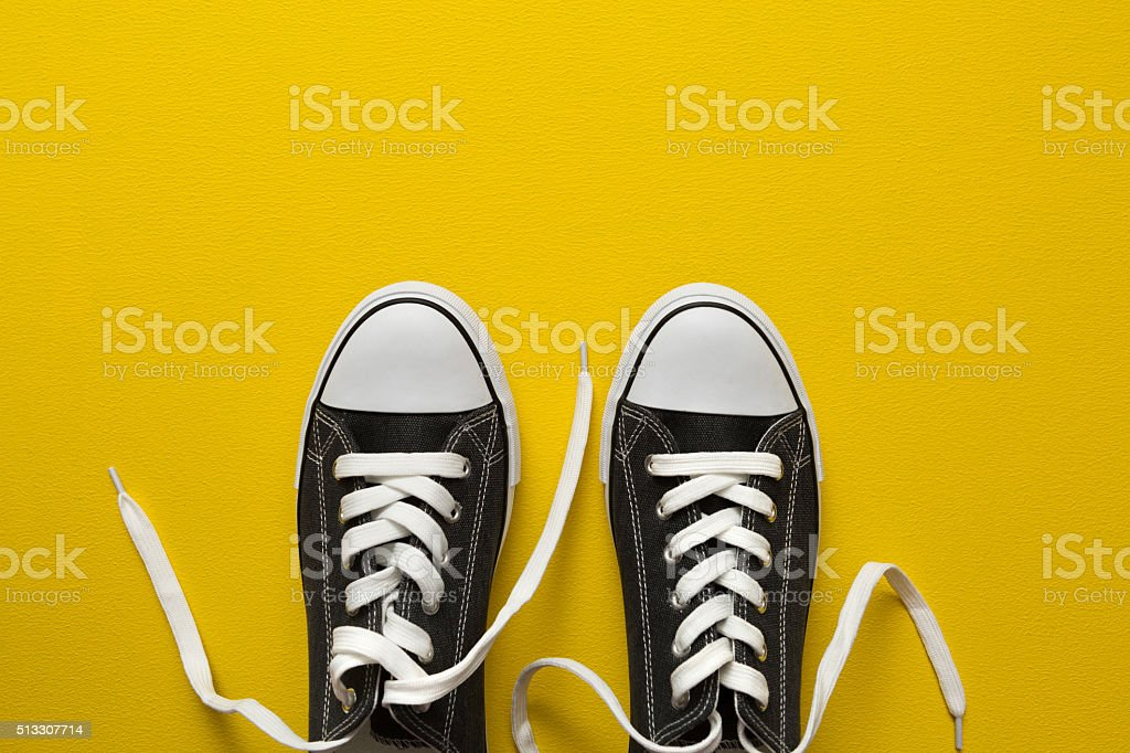 Sneakers on yellow background stock photo