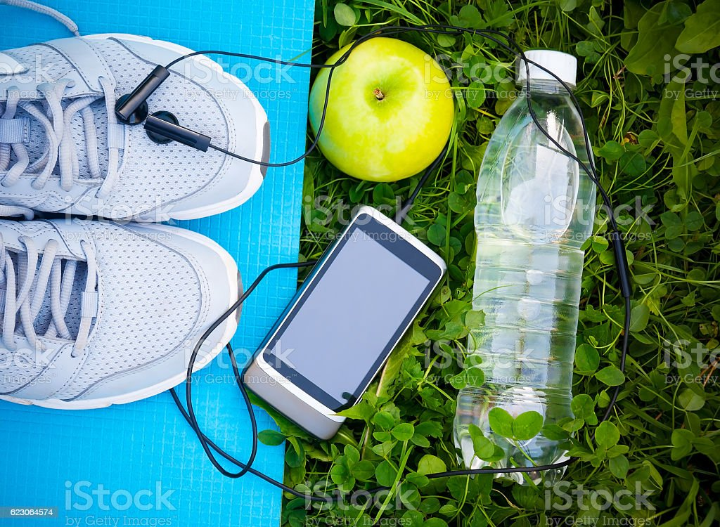 Sneakers on yoga mat  and smartphone with headphones and apple stock photo