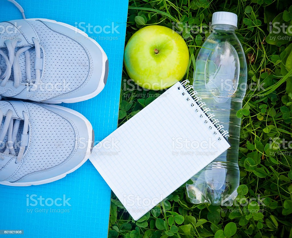 Sneakers on yoga mat, bottle of water and apple stock photo
