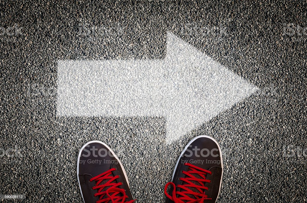 Sneakers standing on a road with arrow stock photo