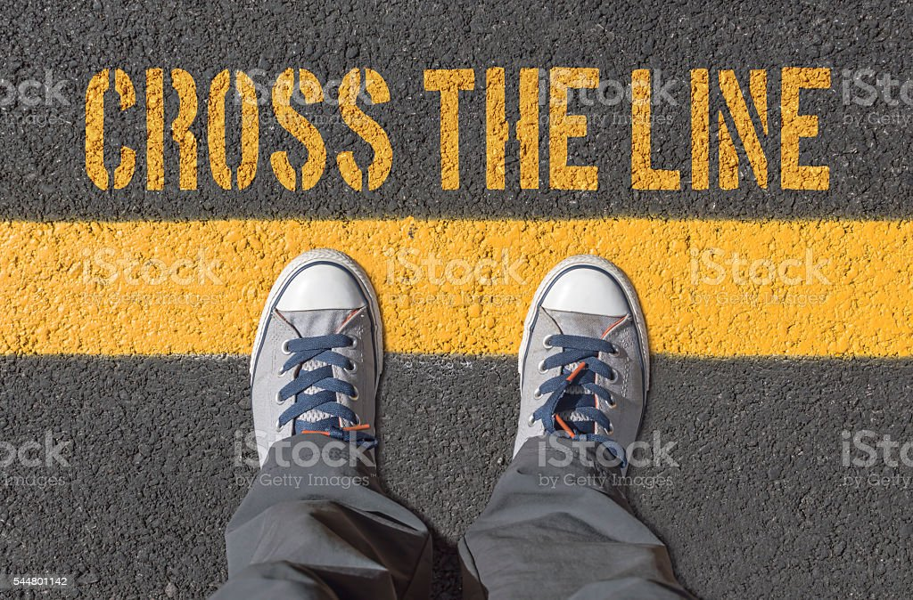 Sneakers standing on the yellow line. stock photo