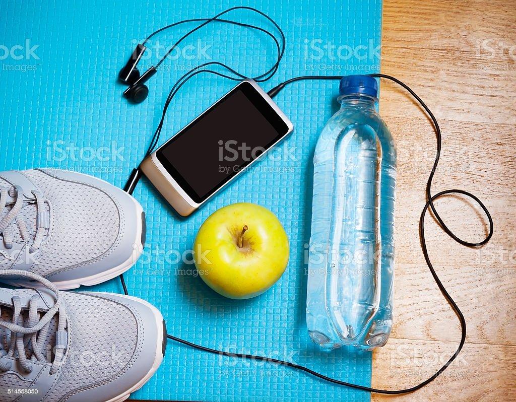 Sneakers, water, apple, smartphone and earphones on yoga mat stock photo
