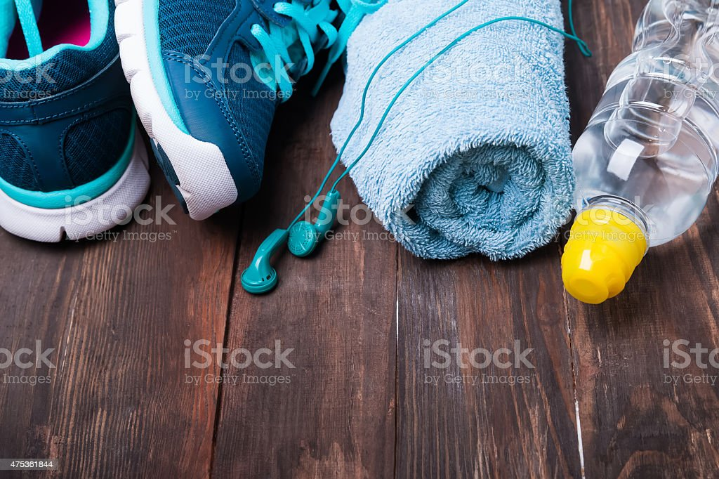 Sneakers, water, towel and earphones on wooden background stock photo
