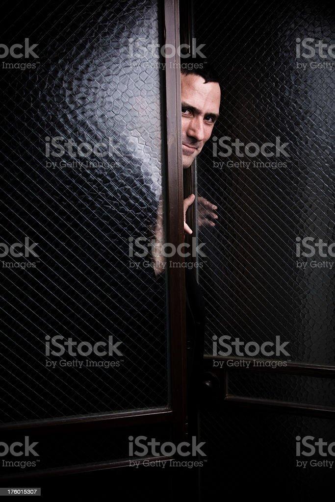Sneaky Man Peeking Through Glass Doors royalty-free stock photo