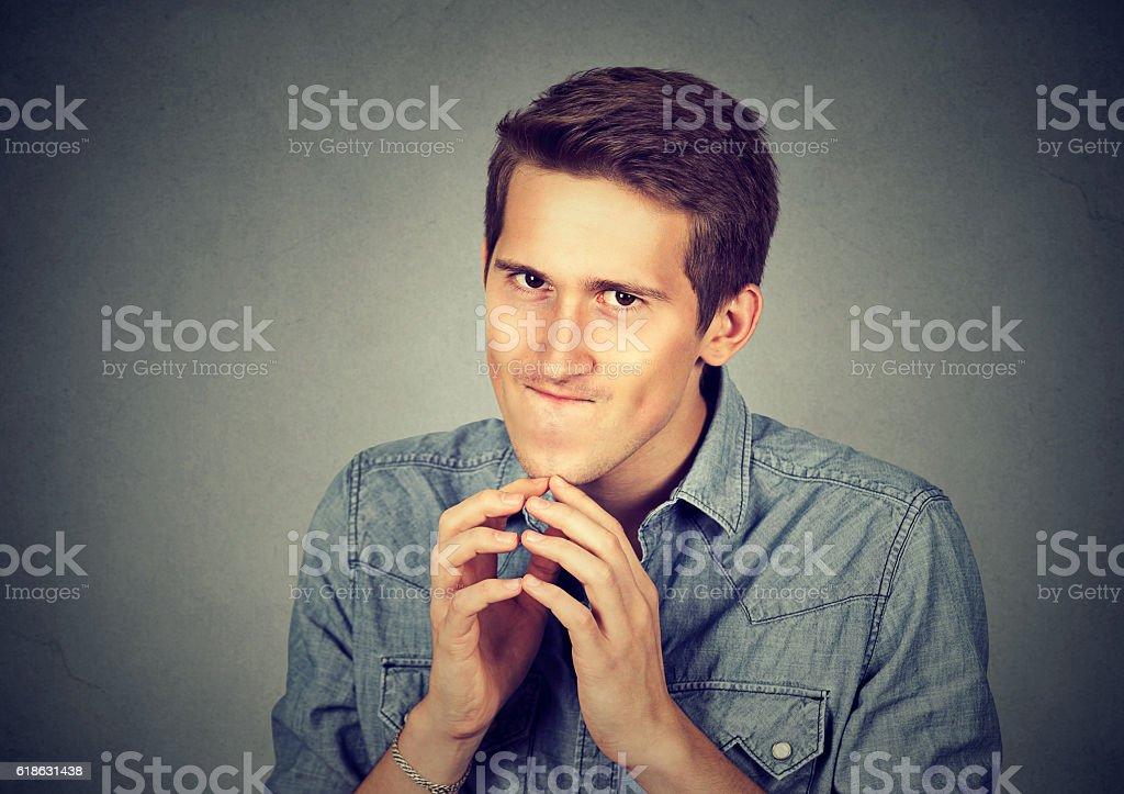 Sneaky scheming young man plotting something stock photo