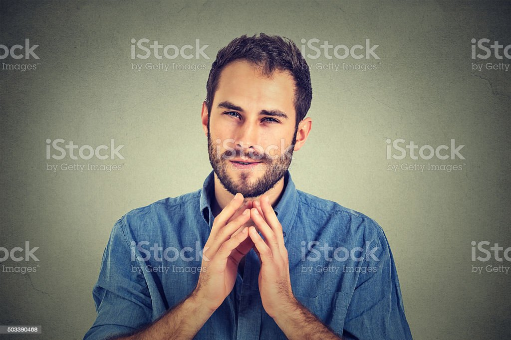 Sneaky scheming young man, worker trying to plot something stock photo