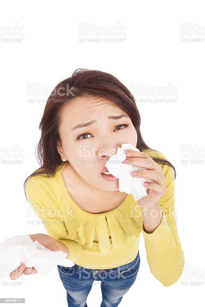 Sneezing and blowing nose,  young woman struggles with cold stock photo