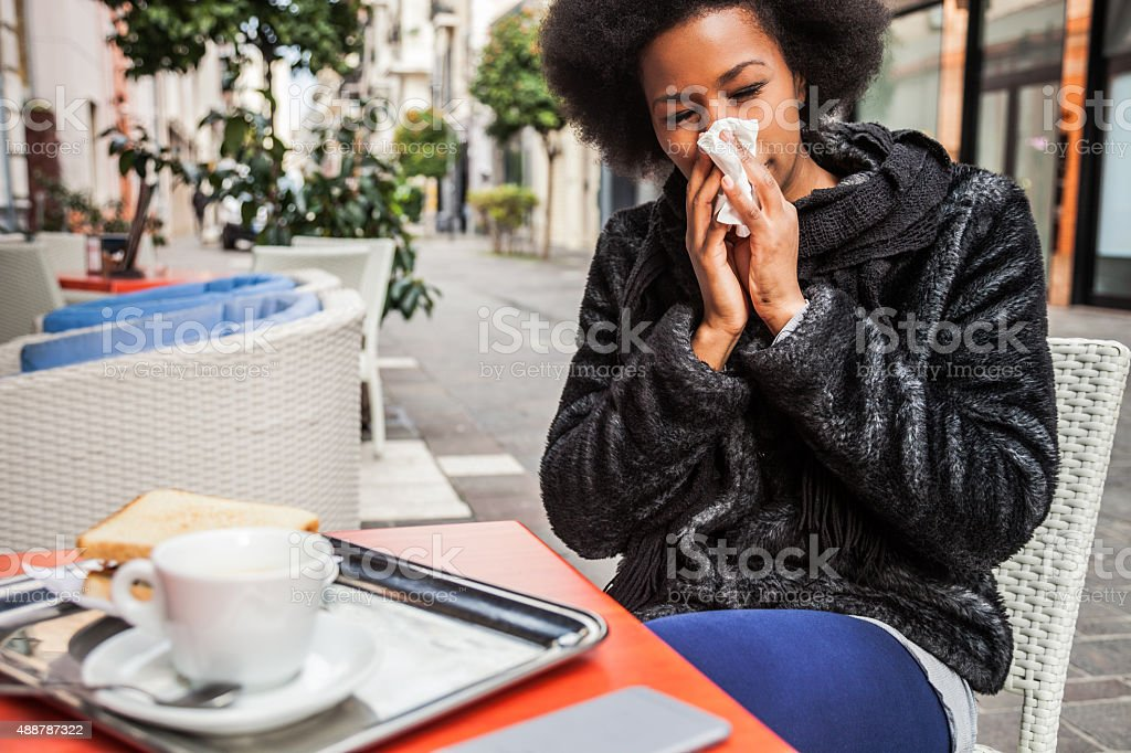 Woman sneezing due to flu during a break in a cafe using an...
