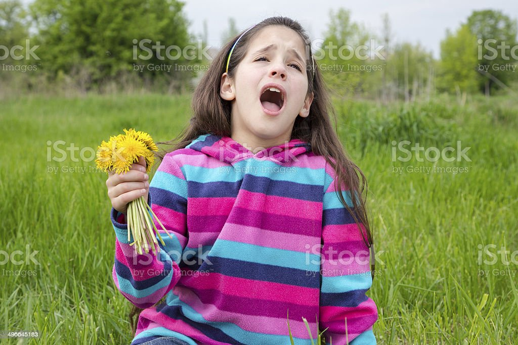 Sneezing girl on meadow with dandelions stock photo