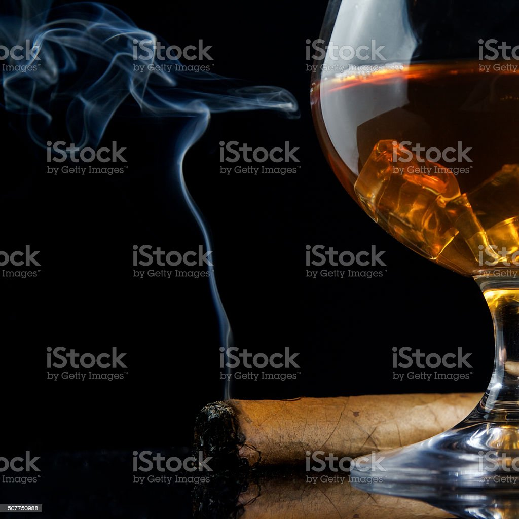 Snifter glass of cognac and cigar stock photo