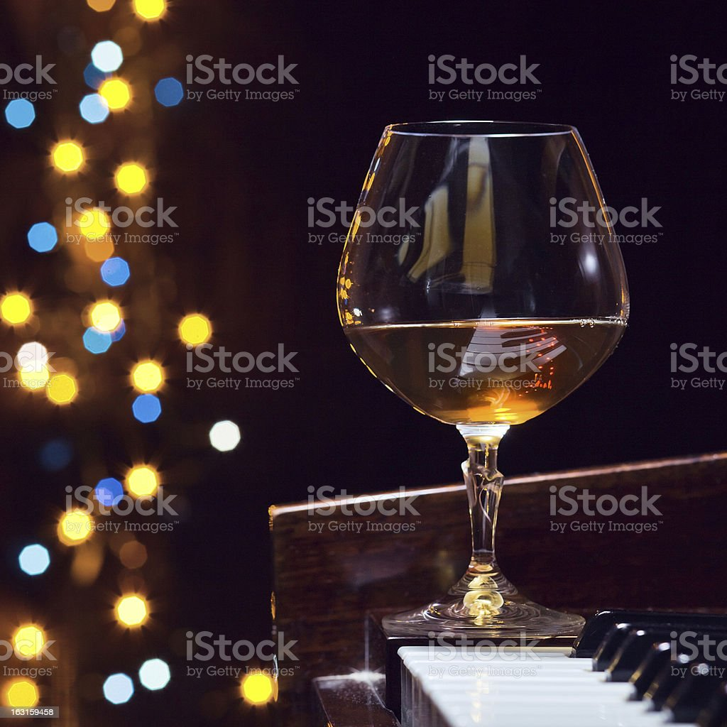snifter with brandy on a piano royalty-free stock photo
