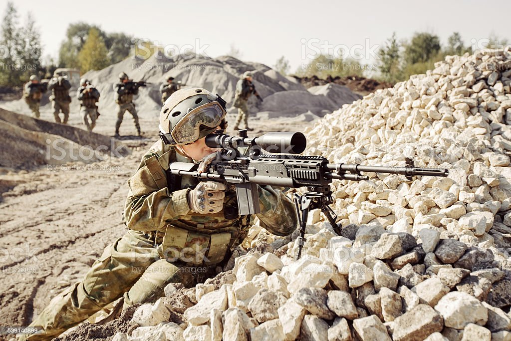 Sniper covers offensive squad of soldiers stock photo