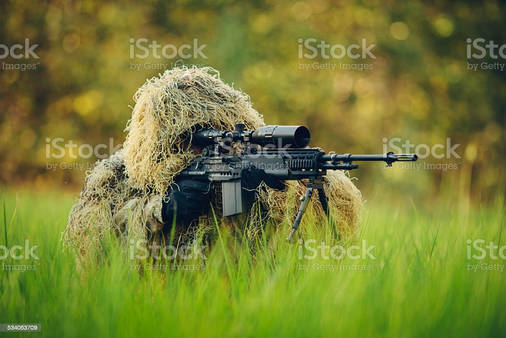 sniper in camouflage suit looking at the target stock photo
