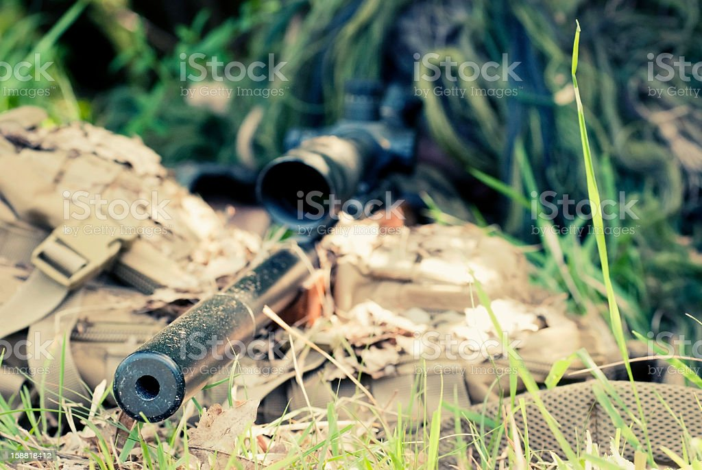 Sniper in Ghillie Suit Hidden and Aiming with Precision Rifle stock photo