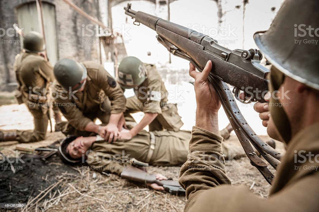 WWII Sniper Providing Cover for Medic Working on Wounded Soldier stock photo
