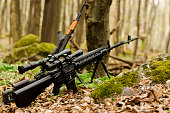 Sniper rifle on bipod on ground background