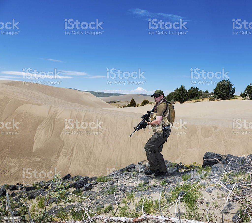 Sniper scouts along a rocky ridge in the desert royalty-free stock photo
