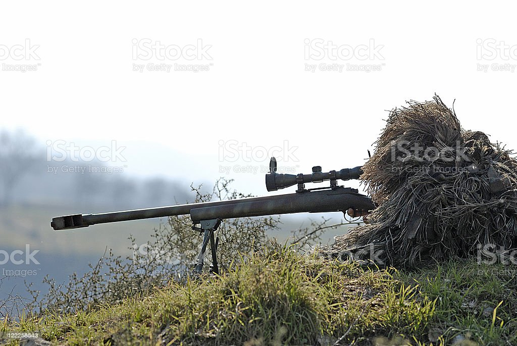 Sniper Soldier Silhouette in Ghillie Suit Aiming with Precision Rifle stock photo