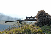 Sniper Soldier Silhouette in Ghillie Suit Aiming with Precision Rifle