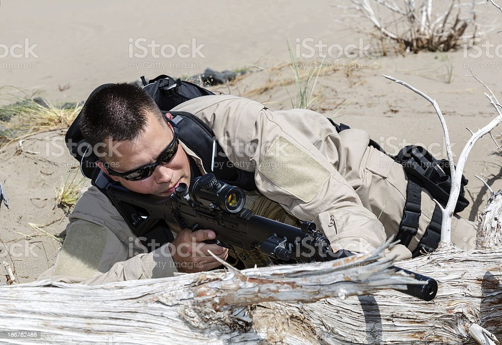 Sniper taking aim concealed behind a log royalty-free stock photo