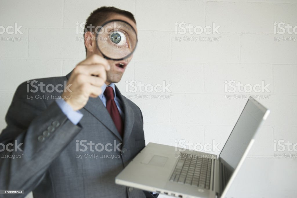 Snooping Businessman Invading Privacy on Laptop with Magnifying Glass royalty-free stock photo