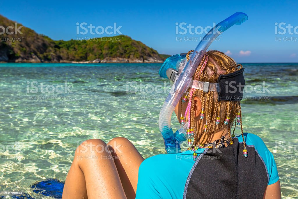 Snorkeler relaxing on tropical beach stock photo