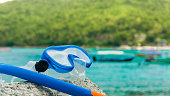 Snorkeling equipment: snorkel and diving google on the stone.