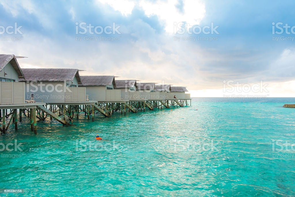 Snorkeling in front of velassaru overwater bungalows in Maldives stock photo