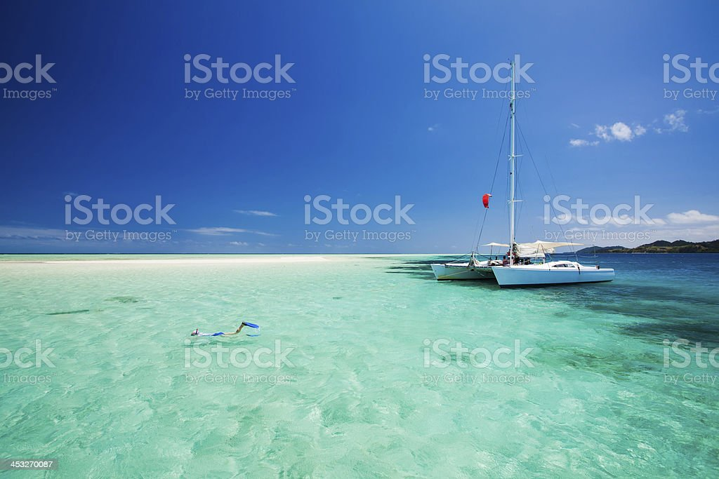 Snorkeling in shallow water off the catamaran stock photo