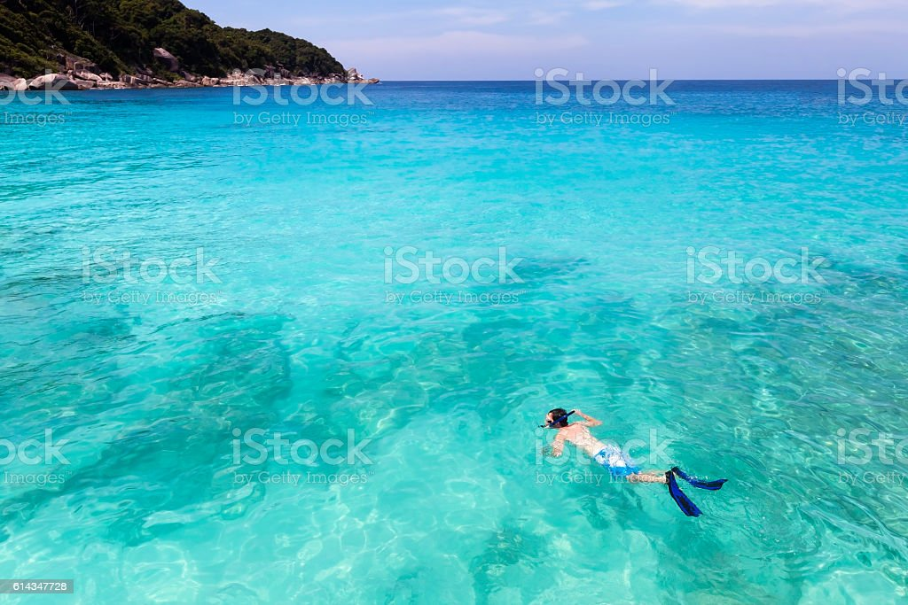 Snorkeller swimming in pristine clear turquoise tropical sea water stock photo