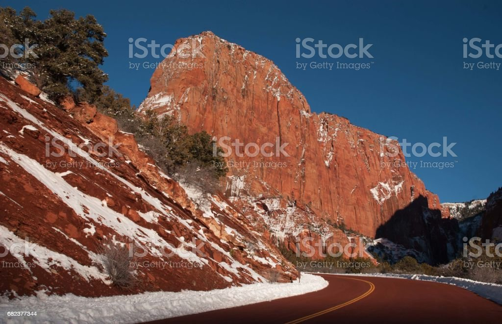 Snow along red rock road into Kolob Canyon in winter with sedimentary rocks in background in Zion National Park Utah stock photo