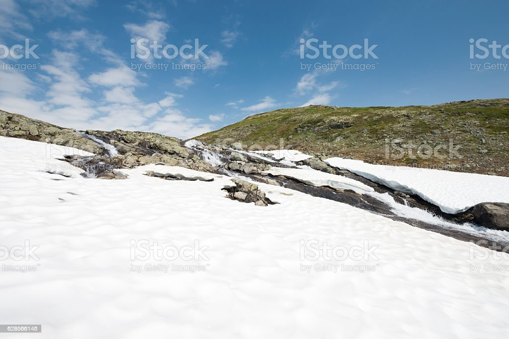 Snow and boulder hike along stream in Norwegian summer mountains stock photo
