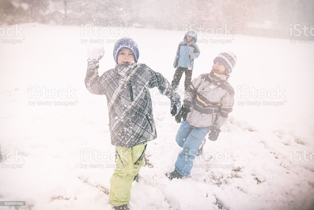 snow ball fight a child throws a snowball stock photo