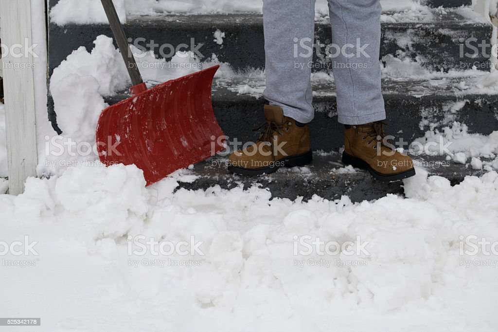 Snow being shoveled by a man in boots stock photo