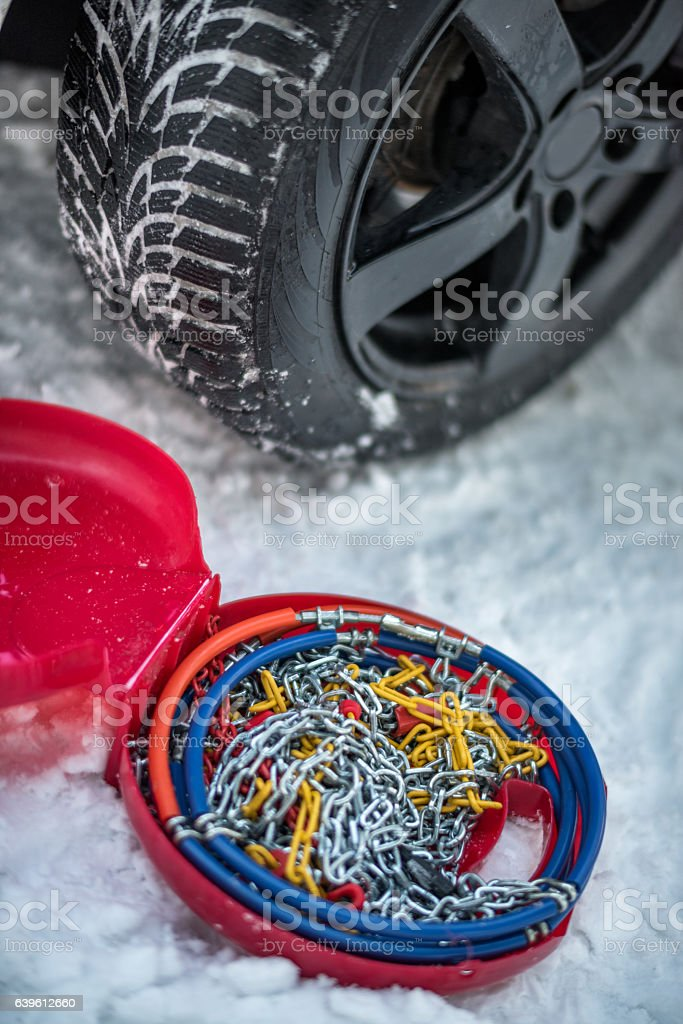 Snow chains next to a car tire stock photo