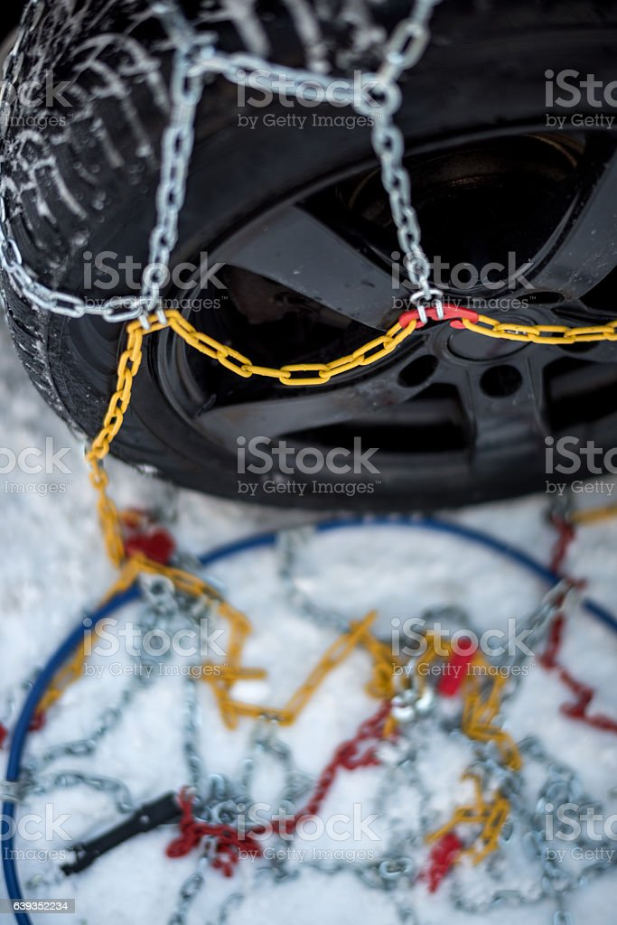 Snow chains on a car tire stock photo