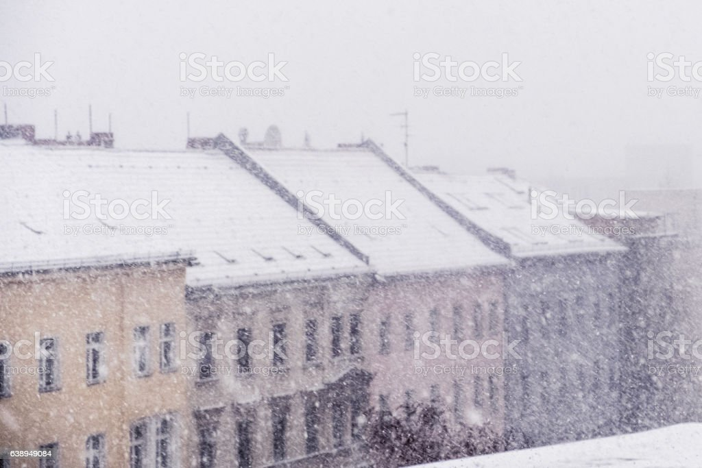 snow cityscape / rooftops during winter snowing stock photo