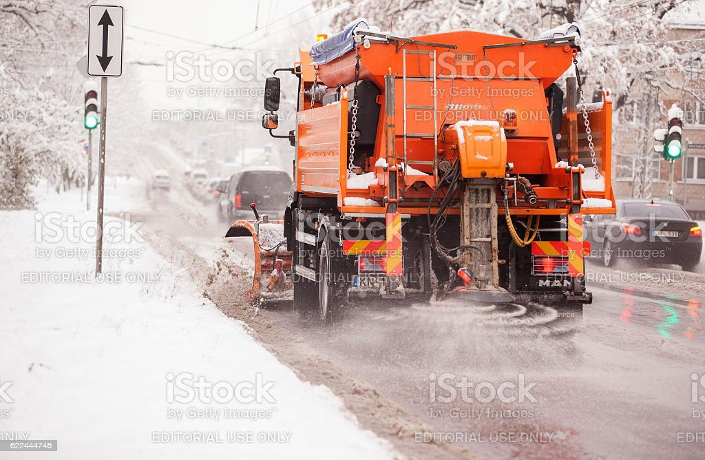Snow cleaner car cleans snowy road and shedds salt stock photo
