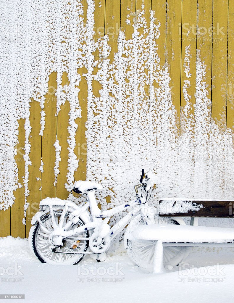 Snow covered bicycle and bench stock photo
