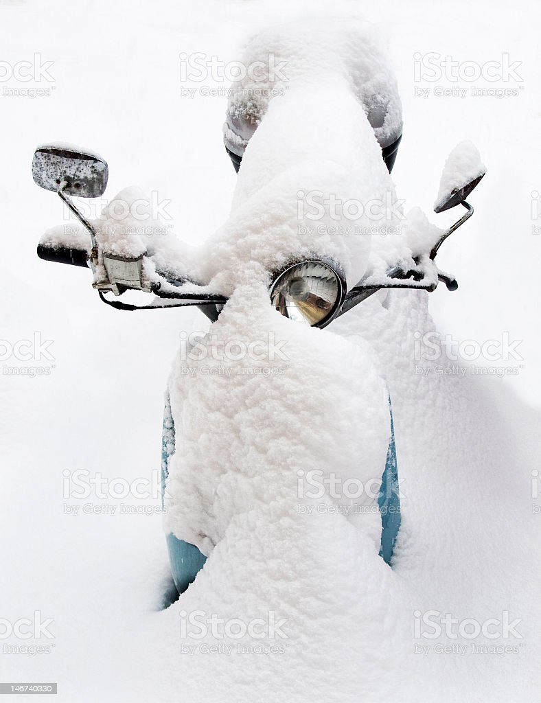Snow covered blue vespa scooter stock photo