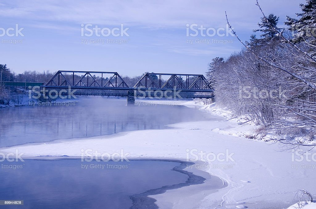 Snow Covered Bridge and Railroad Trestle Over Icy River stock photo