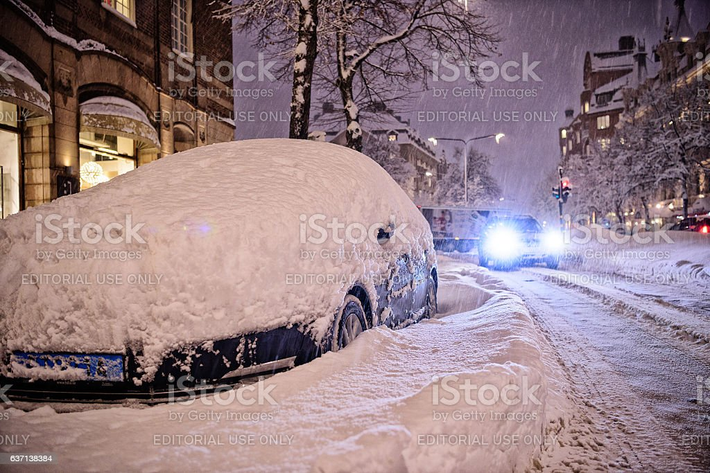 Snow covered car next to zebra crossing. It's snowing. stock photo