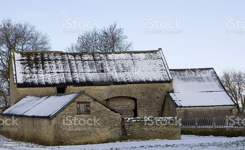 Snow covered Cotswold stone barn in Oxfordshire stock photo