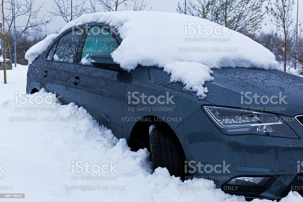 Snow covered dark grey car parked in parking lot. stock photo
