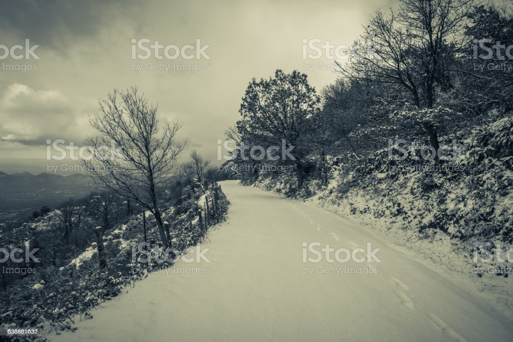 Snow covered mountain road with footsteps and sea view beyond stock photo