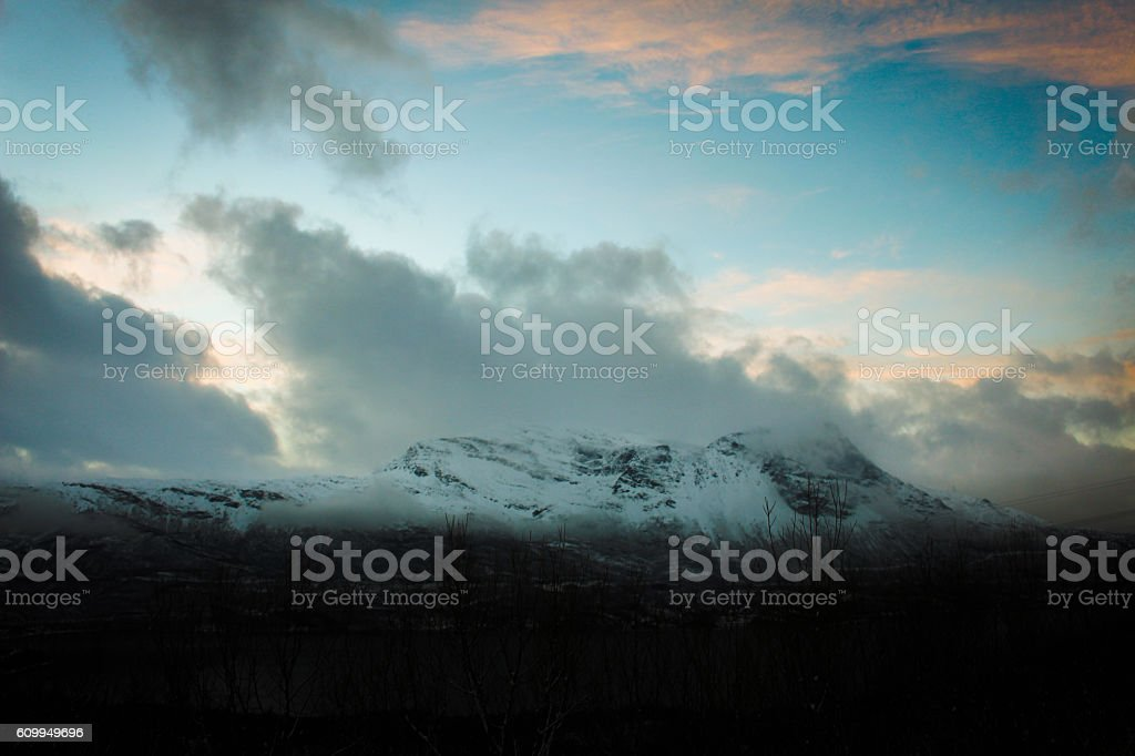 Snow Covered Mountains Against Cloudy Sky stock photo