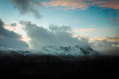 Snow Covered Mountains Against Cloudy Sky