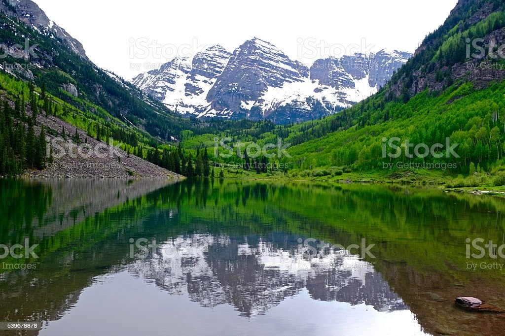 Snow Covered Mountains, Green Trees, Lake and Reflection. stock photo