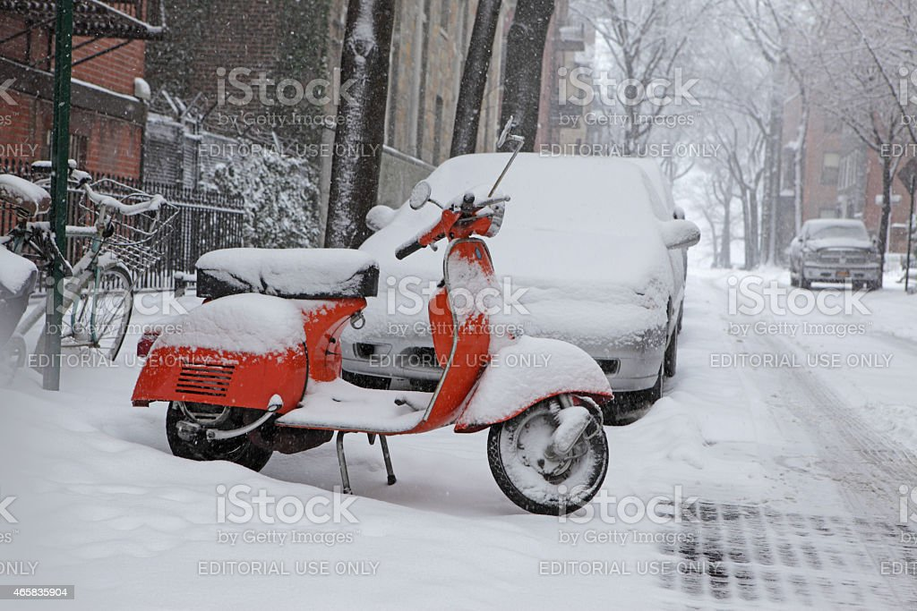 Snow covered orange Vespa scooter parked on Brooklyn winter street stock photo